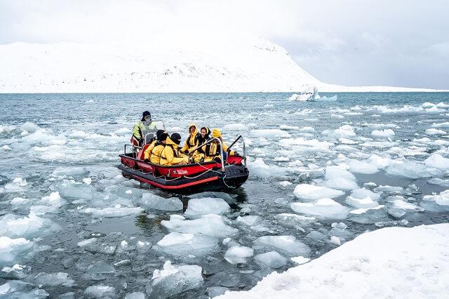 Boot fahren durch das arktische Meer Skitourgehen im Winter-Wunder-Land und nach Eisbären ausschauen machen Reisen wie die Spitzbergen Expedition unvergesslich