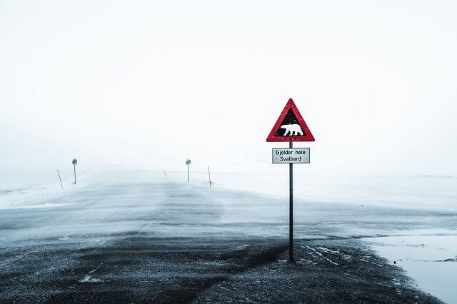 Schilder die vor Eisbären warnen sind auf allen norwegischen Inseln von Spitzbergen im Sommer und Winter an Land verteilt